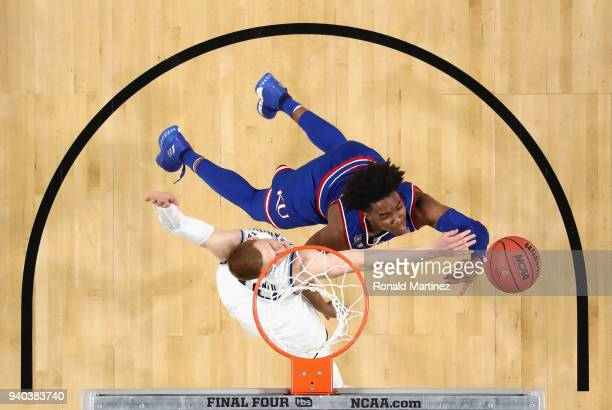 Devonte' Graham of the Kansas Jayhawks drives to the basket against Donte DiVincenzo of the Villanova Wildcats in the first half during the 2018 NCAA...