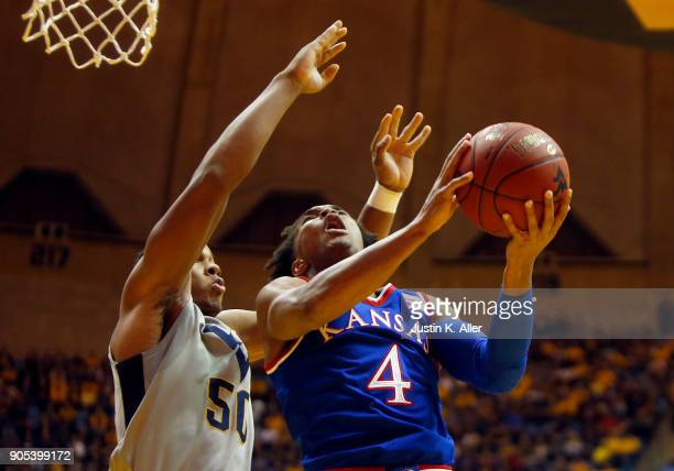 Devonte' Graham of the Kansas Jayhawks drives to the hoop against Sagaba Konate of the West Virginia Mountaineers at the WVU Coliseum on January 15...