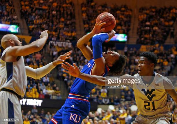 Devonte' Graham of the Kansas Jayhawks drives to the rim against Wesley Harris of the West Virginia Mountaineers at the WVU Coliseum on January 15...
