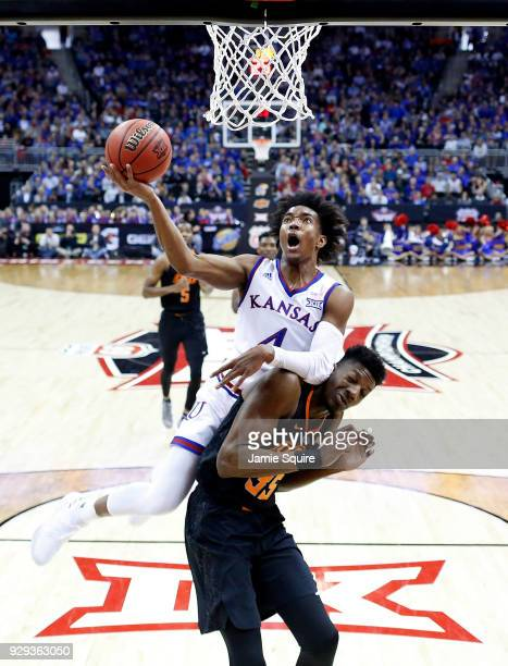 Devonte' Graham of the Kansas Jayhawks drives toward the basket as Yankuba Sima of the Oklahoma State Cowboys defends during the Big 12 Basketball...