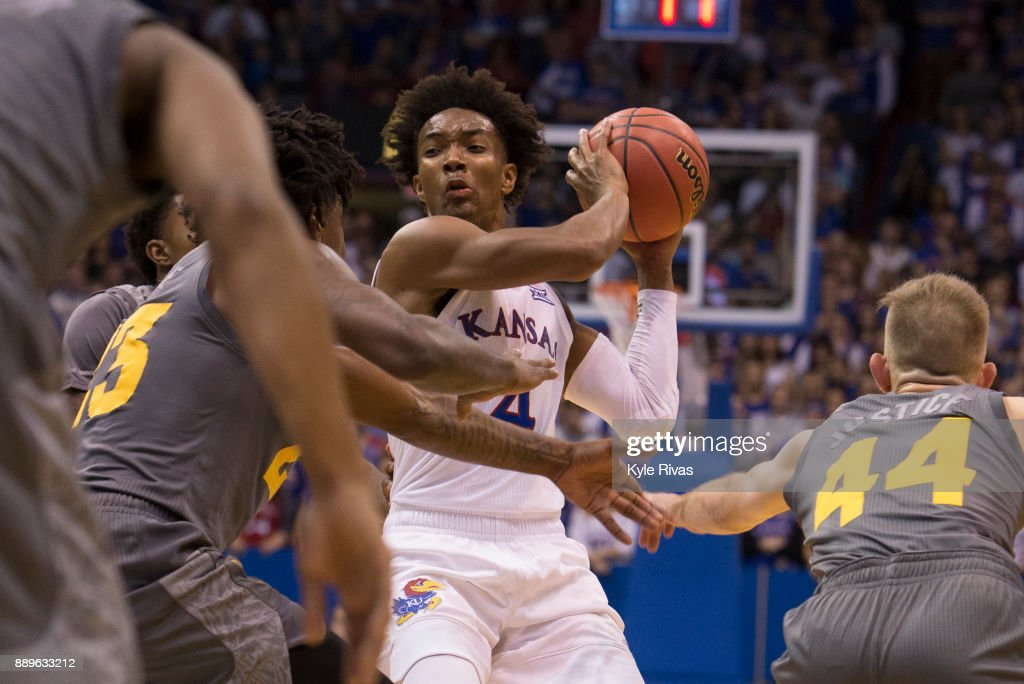 Devonte' Graham #4 of the Kansas Jayhawks gets cut off by the Arizona State Sun Devils defense during the game at Allen Fieldhouse on December 10, 2017 in Lawrence, Kansas.