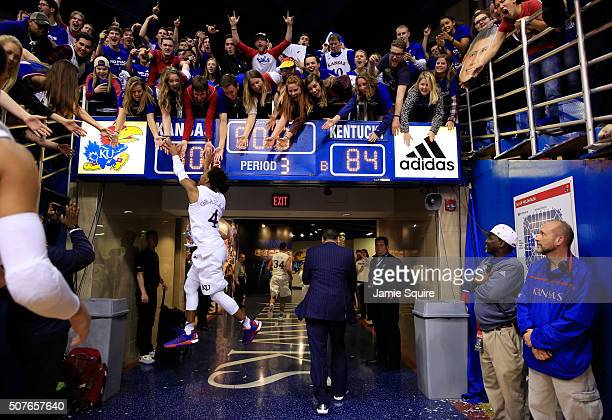 Devonte' Graham of the Kansas Jayhawks leaps to high-five fans as he runs off the floor following the Jayhawks 90-84 victory over the Kentucky...