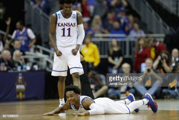 Devonte' Graham of the Kansas Jayhawks lies on the court as Josh Jackson reacts in the second half against the Purdue Boilermakers during the 2017...