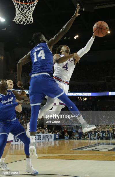 Devonte' Graham of the Kansas Jayhawks shoots against Ismael Sanogo of the Seton Hall Pirates in the first half during the second round of the 2018...
