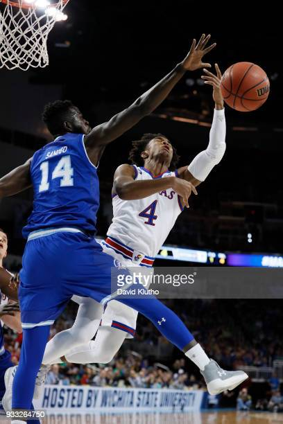 Devonte' Graham of the Kansas Jayhawks shot is blocked by Ismael Sanogo of the Seton Hall Pirates in the second round of the 2018 NCAA Men's...