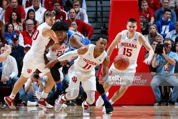 Devonte Green and Zach McRoberts of the Indiana Hoosiers battle for a loose ball against Marvin Bagley III of the Duke Blue Devils in the first half...