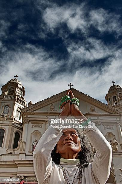 CONTENT] A devoted Catholic woman prays in front of the Quiapo Church in Manila Philippines