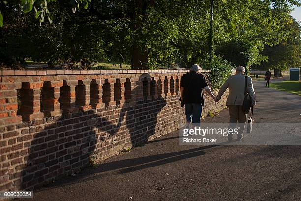 A devoted elderly couple show their love by holding hands as they walk in late afternoon sunshine through Ruskin Park on 8th September 2016 south...