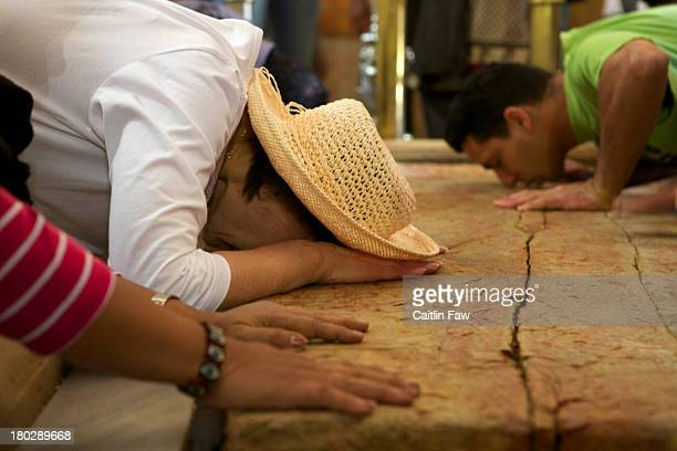 Devoted religious men and women kiss and touch Jerusalem's large slab of holy stone, at the Church or Basilica of the Holy Sepulchre in the Old City.