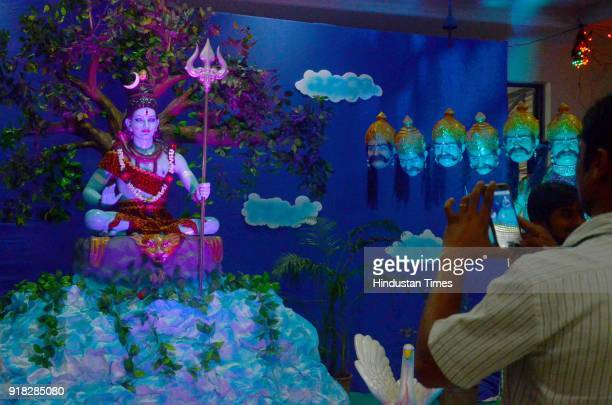 A devotee clicks picture of an idol of lord Shiva during Maha Shivratri celebration at Shiv Vishnu Mandir Vashi on February 13 2018 in Mumbai India...