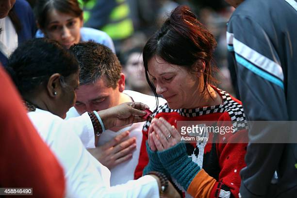 A devotee cries as she approaches Mata Amritanandamayi Devi primarily known simply as Amma the hugging saint for a hug in the event hall Arena on...