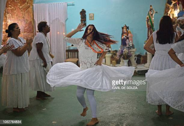 A devotee dances in trance during a ceremony in honour of the Umbanda spirits of Exu and Pombagira in Rio de Janeiro Brazil on October 20 2018...