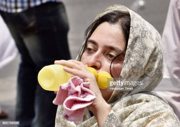 A devotee drinks water during a procession of Lord Jagannath Ratha Yatra chanting Hare Krishna Maha Mantra at Sushant Lok on June 25 2017 in Gurgaon...