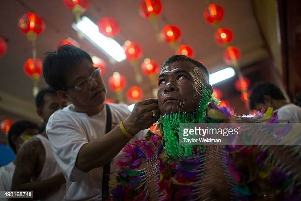 A devotee has decorative needle piercings placed all over his body while in a tranelike state at Bang Neow Shrine on October 18 2015 in Phuket...