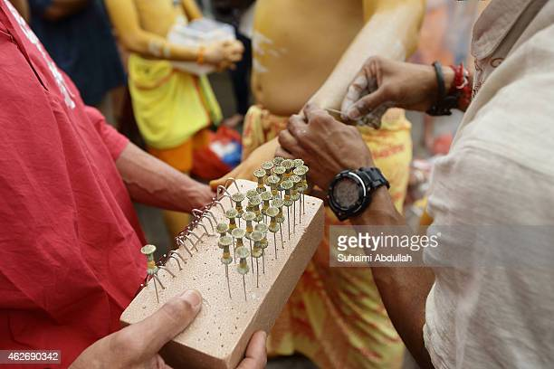 A devotee has his arm pierced with hooks before taking part in the Thaipusam procession at the Sri Srinivasa Perumal Temple at Serangoon Road on...