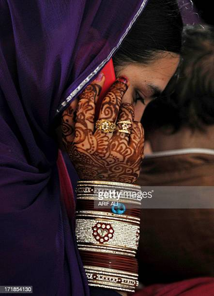 A devotee her hand adorned with henna art talks over her mobile phone at a Sikh shrine in Lahore on June 29 on the 174th death anniversary of...