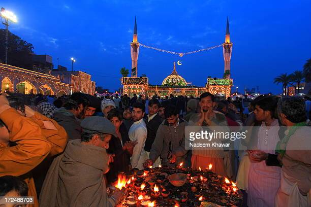 Devotee illuminating the mud made oil lamp at data Darbar on The ocean of annual festival also called urse. People like to use this holly oil of...