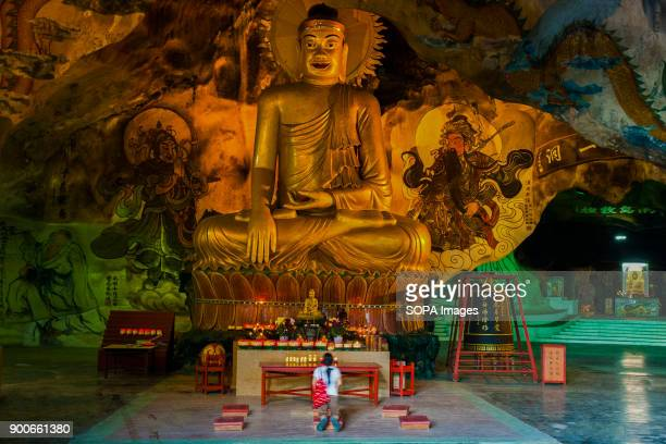 TEMPLE IPOH PERAK MALAYSIA A devotee is seen praying at the huge 40 feet golden Buddha statue at the Perak Tong cave temple Perak Tong cave temple...