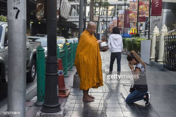 A devotee kneels and prays before a Thai Buddhist monk performing traditional morning alms in Bangkok on December 24 2018