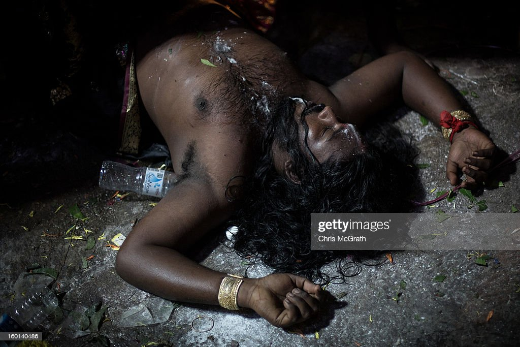 A devotee lays on the ground after passing out inside the Batu Caves during the Thaipusam procession on January 27, 2013 in Batu Caves, Malaysia. Thaipusam is a Hindu festival celebrated on the full moon in the Tamil month of Thai. The festival marks the birthday of Lord Muruga and also commemorates the day Hindu Goddess Parvati gave her son a lance to defeat the evil demon Soorapadamwhen. The festival sees devotees carry milk pots to seek forgivness and some will carry a 'Kavadi' many of which are attached via, strings, hooks, and skews pierced into the carriers skin.