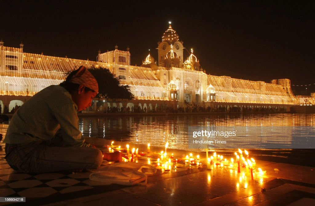 A devotee lighting the candles in Harmandar Sahib Complex which illuminating with electric lamps on the eve of Diwali festival, on November 12, 2012 in Amritsar, India.