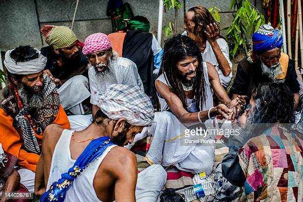 A devotee lights a friend's chillum as they rest during a pilgrimage to Ajmer on May 8 2012 in New Delhi India Sufi pilgrims from all over the world...