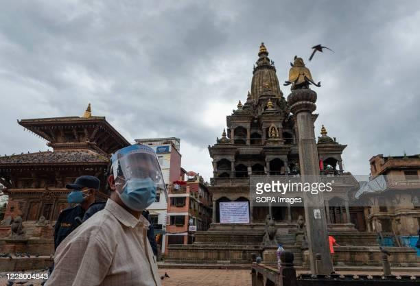 A devotee looks on while wearing a face shield and a face mask during the festival at Hanuman Dhoka Sadak near Kathmandu Durbar Square Krishna...