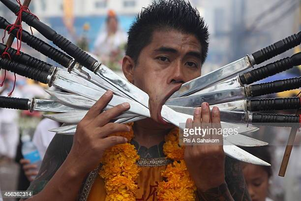 A devotee of a Chinese Shrine with swords pierced through his cheeks takes part in a street procession during the Phuket Vegetarian Festival The...