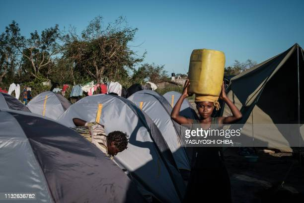 A Devotee of Jehovah's Witnesses carries a water tank at an evacuation site where already 352 people stay after the cyclone Idai hit the region in...