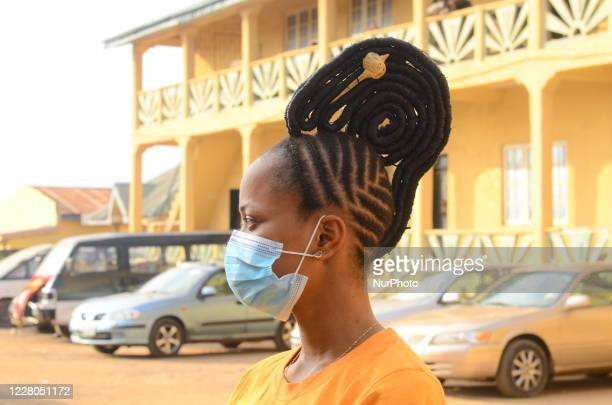 Devotee of river goddess Osun with a nose mask pose for photograph during the annual Osun-Osogbo festival in honour of her in Osogbo, Nigeria, on...