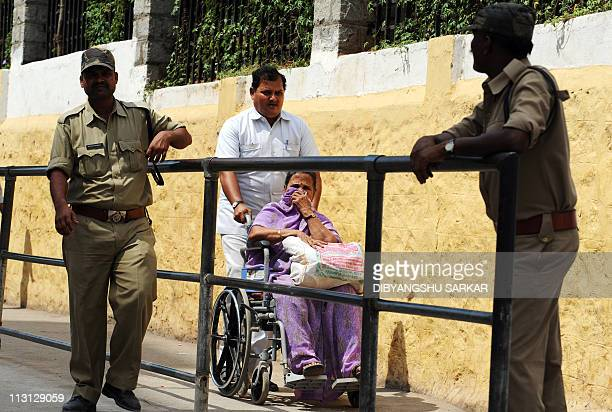 A devotee of Satya Sai Baba on a wheelchair is pushed past security personnel towards his Ashram to participate in a special prayer after his death...