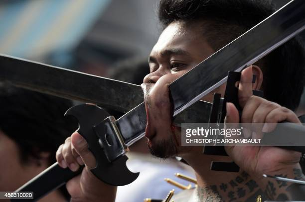A devotee of the Chinese Bang Neow Shrine with swords inserted into his cheeks takes part in a street procession during the annual Vegetarian...