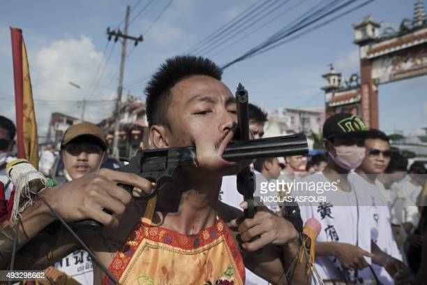 A devotee of the Chinese Jui Tui Shrine has his cheeks pierced with guns as he attends a street procession during the annual Vegetarian Festival in...