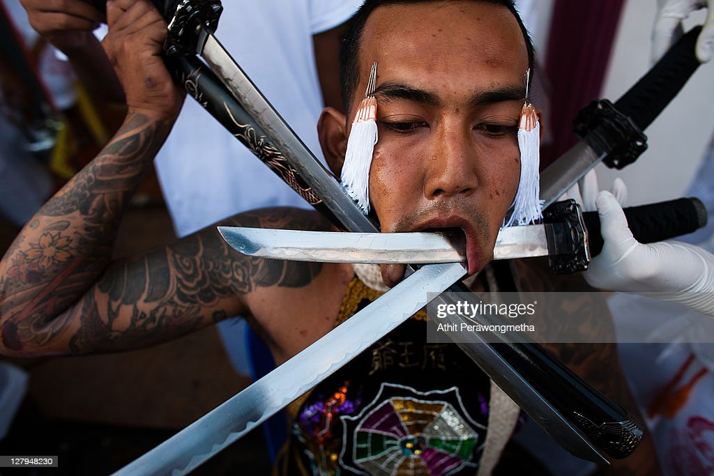 A devotee of the Chinese shrine of Kathu Shrine, pieaces his cheeks with swords during during a procession of Vegetarian Festival on October 4, 2011 in Phuket, Thailand.Ritual Vegetarianism in Phuket Island traces it roots back to the early 1800's. The festival begins on the first evening of the ninth lunar month and lasts for nine days. Participants in the festival perform acts of body piercing as a means of shifting evil spirits from individuals onto themselves and bring the community good luck.