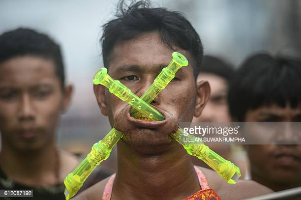A devotee of the Nine Emperor Gods parades through the town of Phuket with recorders pierced through his cheeks during the annual Phuket Vegetarian...