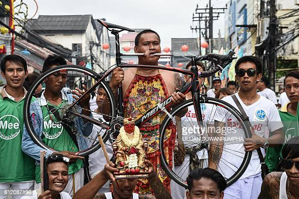 TOPSHOT A devotee of the Nine Emperor Gods parades through the town of Phuket with a bicycle attached to his cheek during the annual Phuket...