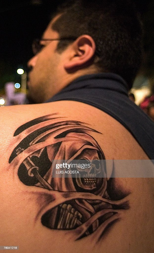 A devotee of the 'Santa Muerte' , shows his tattoo at the