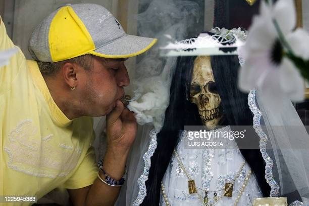 A devotee of the 'Santa Muerte' throws smoke at a figure of the goddess at the shrine in her honour in the popular Tepito shantytown in Mexico City...