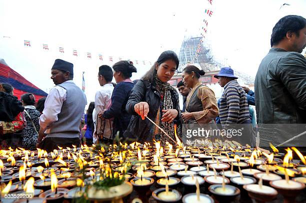 Devotee offering butte lamps at the Boudhanath stupa one of the largest stupas in the world during celebration the 2560th Buddha Purnima festival...