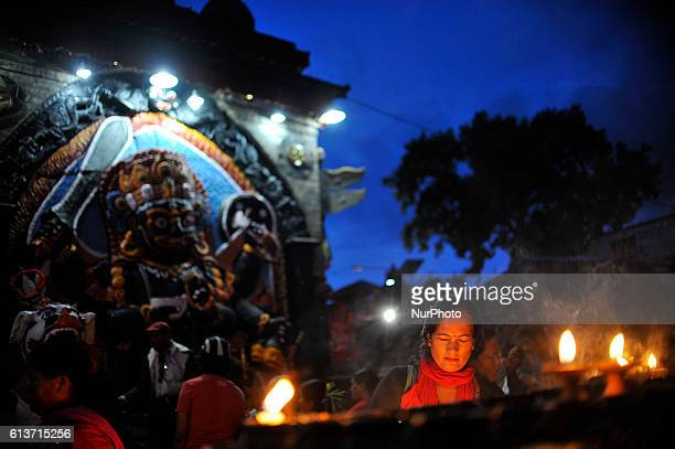 Devotee offering butter lamps infornt of Kaal Bhairab on the occasion of Navami ninth day of Dashain Festival at Basantapur Durbar Square Kathmandu...