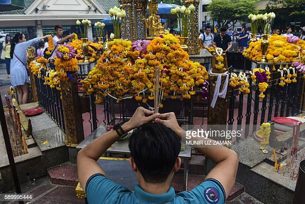 Devotee offers prayers at the Erawan Shrine, a popular tourist landmark in Bangkok on August 16 the eve of the first anniversary of a bomb attack...