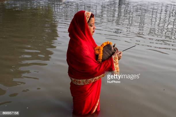 A devotee performing her rites and rituals for the well being during the Chhath puja celebrations in Kolkata West Bengal on october 26 2017