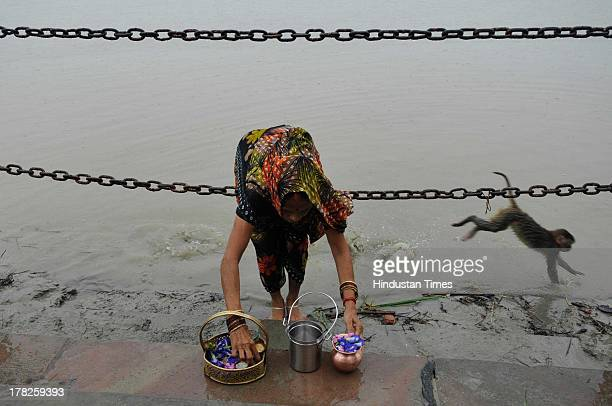 Devotee prays at Saryu Ghat during rainfall on August 27, 2013 in Ayodhya, India. Two days after the failed Parikarma attempt by Vishwa Hindu...