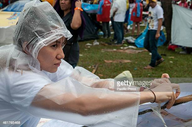 A devotee prepares her makeshift roof out of sacks as temporary shelter against the rain during the rainy Pope's mass in Luneta