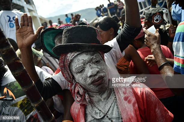 A devotee pretending to be the spirit known as a Gede smiles during a ceremony honoring the Haitian voodoo spirits of Baron Samdi and Gede on the Day...