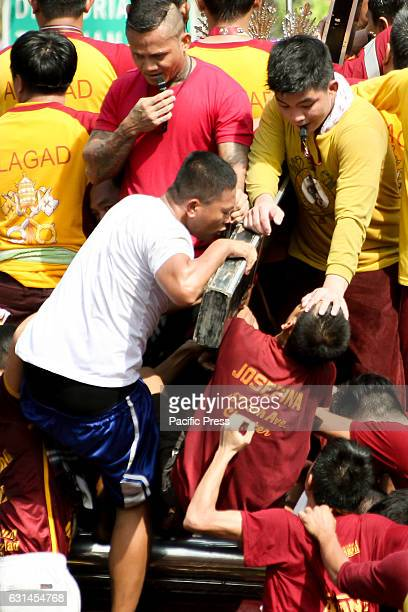 AVE MANILA NCR PHILIPPINES A devotee reverently kisses the cross of the miraculous Icon of the Black Nazarene as another devotee is given a blessing...