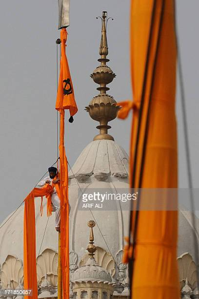 A devotee secures a cloth over a pole at a Sikh shrine in Lahore on June 29 on the 174th death anniversary of Maharaja Ranjit Singh Singh was also...