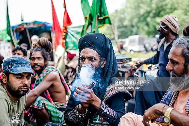 A devotee smokes a chillum as he rests during a pilgrimage to Ajmer on May 8 2012 in New Delhi India Sufi pilgrims from all over the world are making...