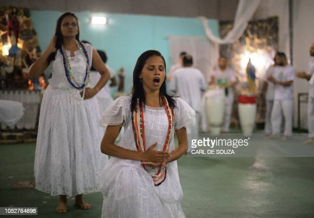 A devotee speaks in trance during a ceremony in honour of the Umbanda spirits of Exu and Pombagira in Rio de Janeiro Brazil on October 20 2018...
