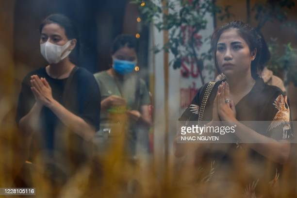 Devotee stands next to anothr woman wearing a face mask as she offers prayers at Quan Su pagoda in Hanoi on August 19, 2020.